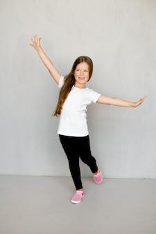 Tシャツに長髪のかわいい若い子供と腕を組んで立っているスウェットパンツ