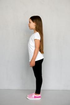 プロファイルに立っている白いtシャツと黒いスウェットパンツの長い髪のかわいい若い子