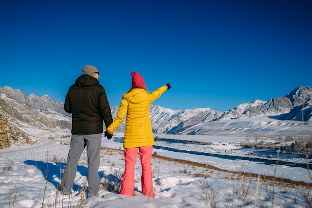 Cute young couple in bright down jackets by beautiful winter mountain scenery with copy space. christmas holidays in mountains. man and woman looking at snowy peaks.