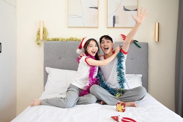 ベッドでクリスマスを祝うかわいい若いカップル