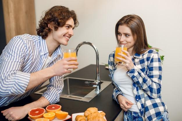 집 부엌에서 신선한 오렌지 주스를 마시는 귀여운 젊은 부부.