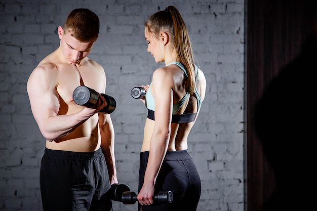 Cute young couple exercising with dumbbells in the gym