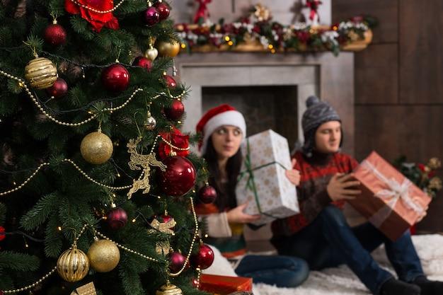 크리스마스 트리 앞 양탄자에 앉아 흔들면서 상자를 귀에 대고 크리스마스 선물을 추측하는 귀여운 젊은 부부