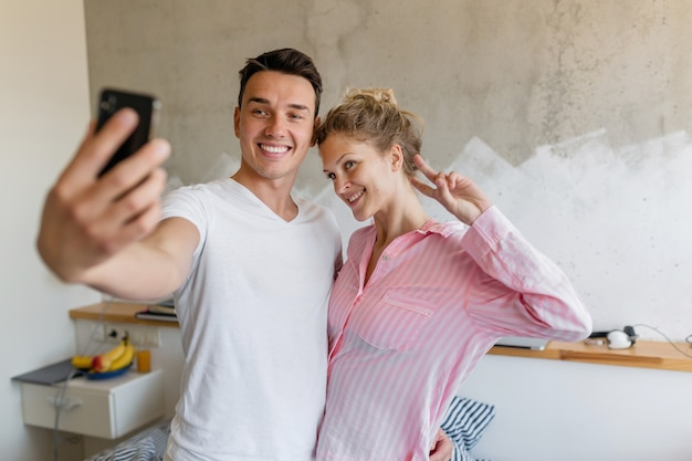 Cute young couple having fun on bedroom in morning, man and woman making selfie photo wearing pajamas