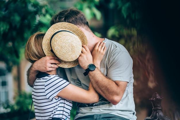 Милая молодая пара обнимает целоваться с соломенной шляпе