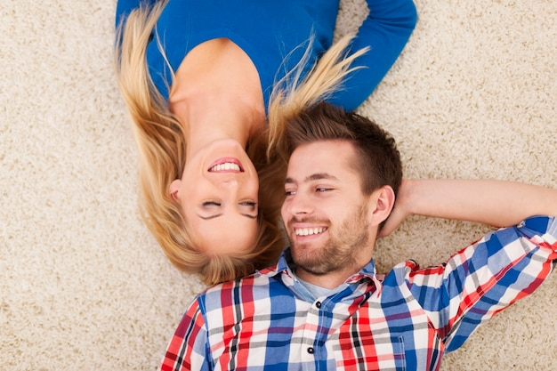 Cute young couple lying on carpet and look at each other