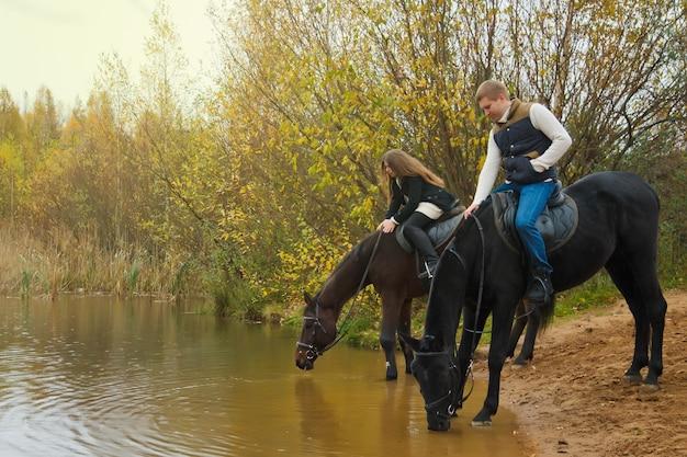 호수가 숲에서 말을 타고 귀여운 젊은 부부. 말은 연못에서 물을 마시고, 사람들은 갈기를 쓰다듬습니다. 가 공원에서 라이더입니다. 야외 승마, 스포츠 및 레크리에이션의 개념입니다. 복사 공간