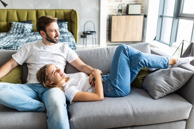Милая молодая пара отдыхает на диване у себя дома в гостиной