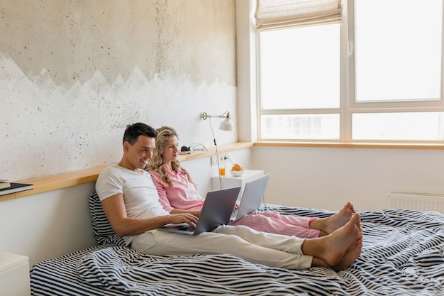 Cute young couple sitting on bed in morning, man and woman working on laptop