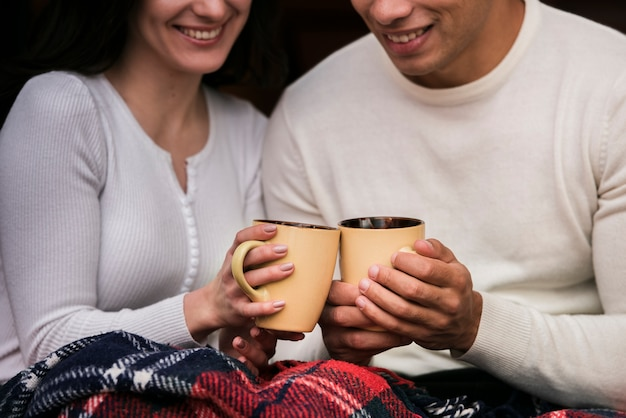 Cute young couple with hot drinks