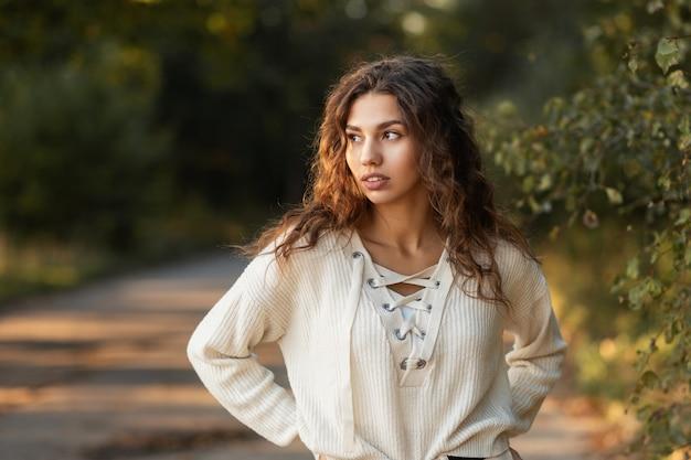 니트 스웨터에 자연의 아름다움을 가진 귀여운 곱슬 머리 소녀는 자연 공원에서 산책
