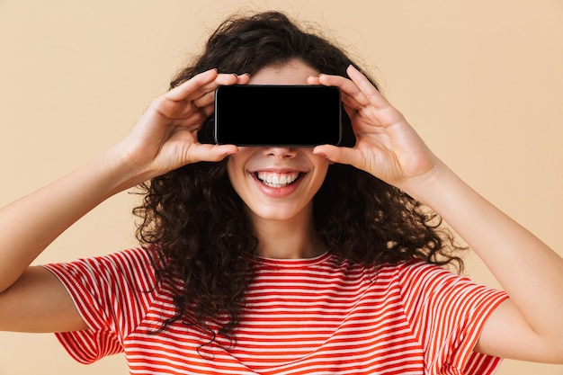 目を覆っている携帯電話でディスプレイを表示しているかわいい若い巻き毛の女性。
