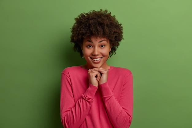 かわいい若い暗い肌の巻き毛の女性モデルは、あごの下で手を一緒に押し続け、優しく微笑んで、白い完璧な歯を示し、バラ色の服を着て、緑の壁に対してモデル