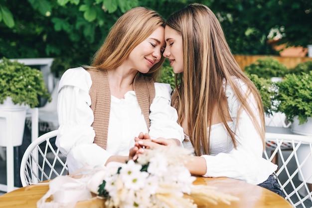 カフェで愛情を込めて母親を抱きしめるかわいい若い娘
