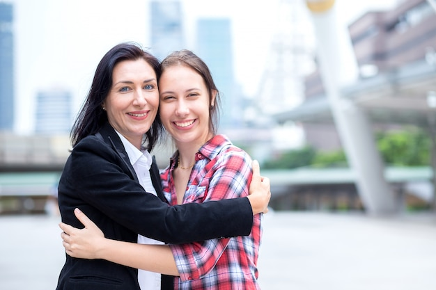 Cute young daughter hug her mother in city after her mom come ba
