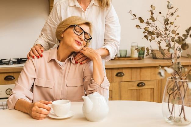 キッチンで愛情を込めて母親を抱き締めるかわいい若い娘。娘と一緒にキッチンで高齢のシニア成熟した女性。