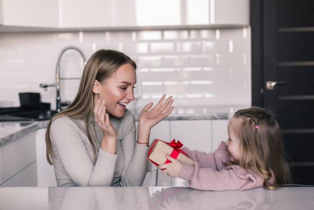 Cute young daughter offering gift to her mother in the in the kitchen. mother day.
