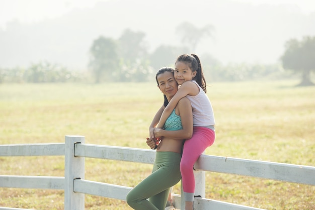 Carina giovane figlia su un giro sulle spalle con la madre che trascorre del tempo in campagna. famiglia felice sul prato in estate in natura. sport e fitness all'aperto, apprendimento degli esercizi per lo sviluppo dei bambini.