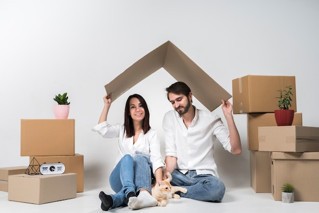 Cute young family posing next to cardboard boxes