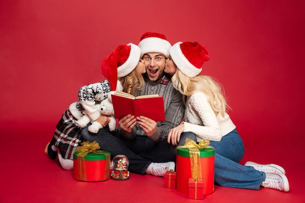 Cute young family wearing christmas hats sitting isolated