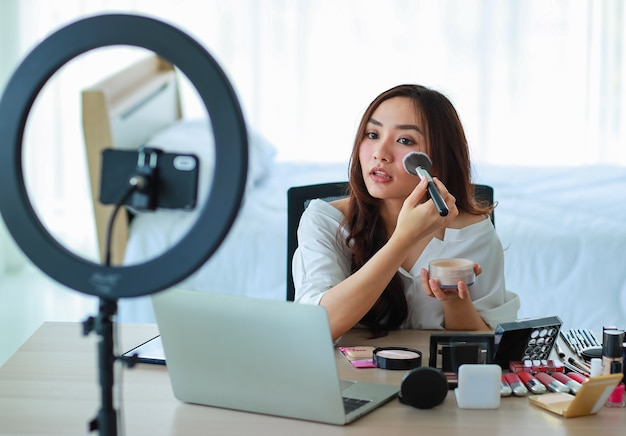 Cute and young female blogger or vlogger broadcast or recording video for beauty blog beauty and cosmetics. influencer lives video to social network. concept for blogging, videoblog, makeup.