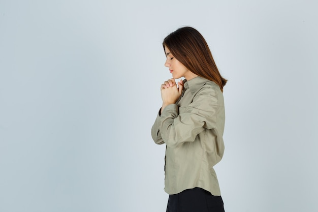 Cute young female clasping hands in praying gesture in shirt, skirt and looking hopeful .