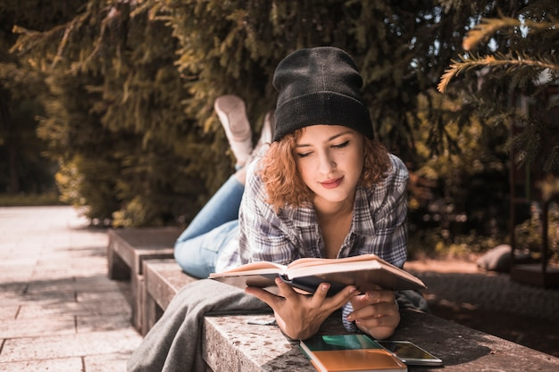 Cute young female in hat reading book in park