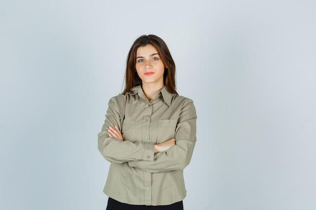 シャツ、スカートで腕を組んで、賢明に見えるかわいい若い女性。正面図。