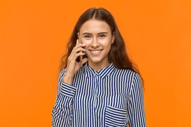 그녀의 귀에 휴대 전화를 들고 즐겁게 웃는 귀여운 젊은 여성, 남자 친구와 이야기