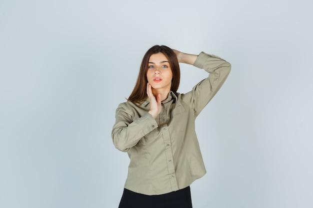 シャツ、スカート、繊細な正面図で彼女のあごに触れながら頭の後ろで手をつないでかわいい若い女性。