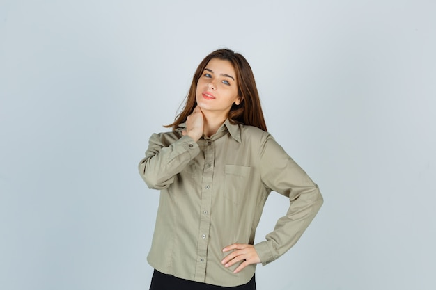 Милая молодая самка держит руку на шее в рубашке, юбке и выглядит веселой, вид спереди.