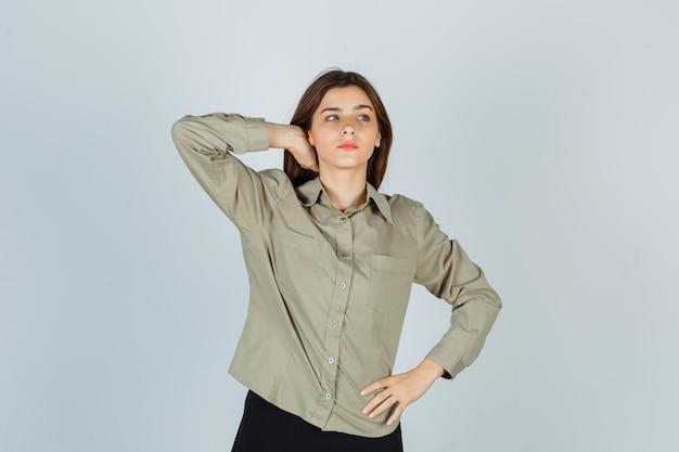 셔츠를 입은 귀여운 젊은 여성, 치마에 손을 잡고 생각에 잠긴 앞모습.