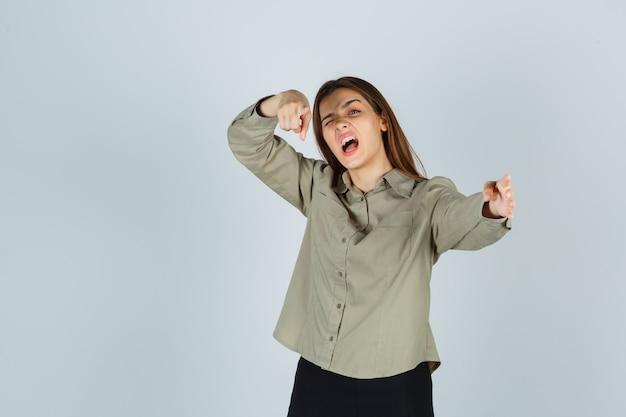 셔츠를 입은 귀여운 젊은 여성, 치마를 입고 카메라를 가리키며 비명을 지르고, 깜박거리고, 정력적인 모습을 보입니다.