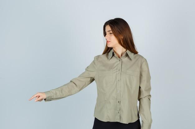 셔츠를 입은 귀여운 젊은 여성, 치마가 아래를 가리키고 초점이 맞춰져 있는 앞모습.