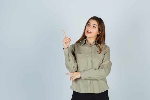 셔츠를 입은 귀여운 젊은 여성, 치마가 위로 향하고 궁금해 보이는 전면 보기.