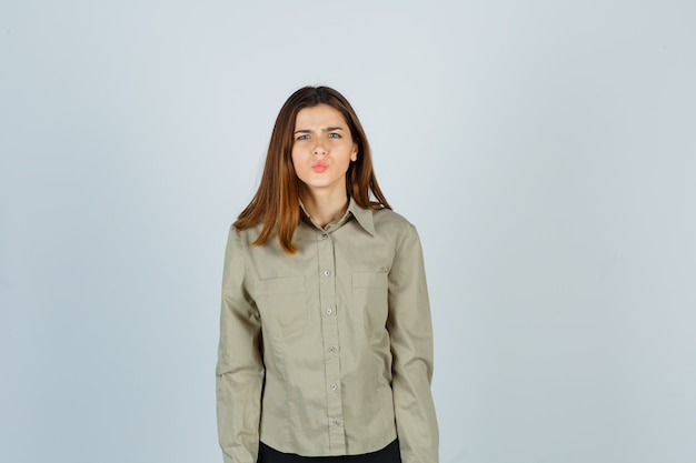 Cute young female keeping lips folded while frowning face in shirt and looking perplexed. front view.