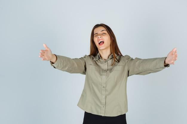 귀여운 젊은 여성이 팔짱을 끼고 셔츠, 치마를 입고 활기차게 앞을 바라보는 동안 팔을 벌리고 있습니다.