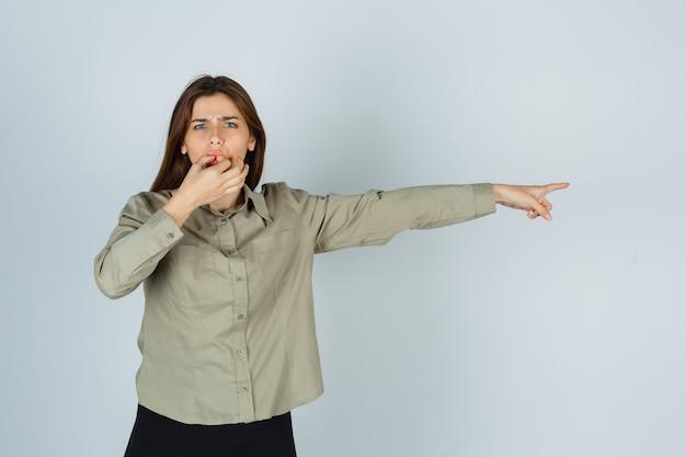 셔츠, 치마에 손가락으로 휘파람을 불고 우울해 보이는 동안 오른쪽을 가리키는 귀여운 젊은 여성. 전면보기.