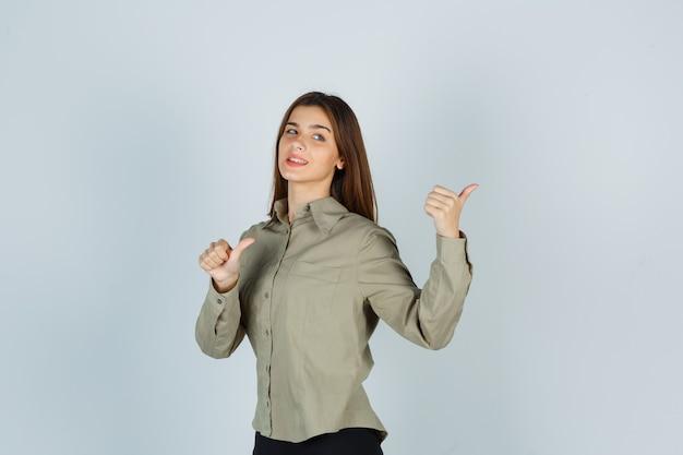 Carina giovane donna in camicia che punta indietro con i pollici e sembra sicura, vista frontale.