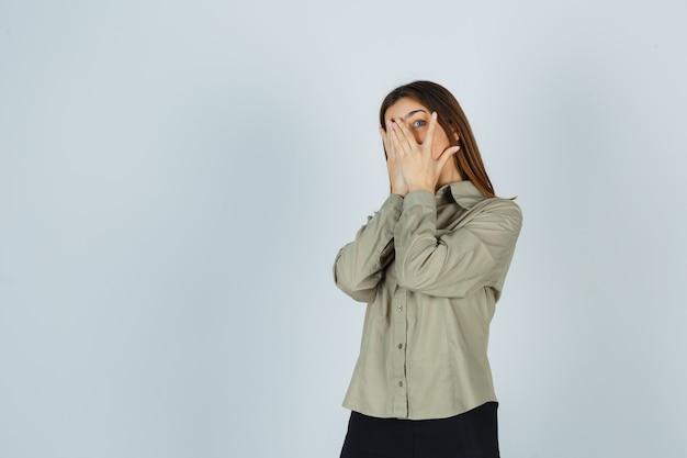 Carina giovane donna in camicia, gonna che guarda tra le dita e sembra spaventata, vista frontale.