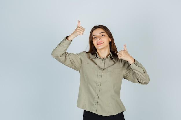 Carina giovane donna in camicia, gonna che mostra il doppio pollice in alto e sembra felice, vista frontale.