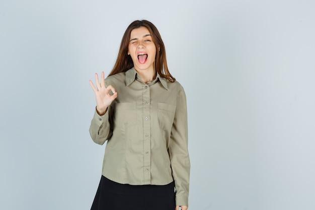 Carina giovane donna in camicia, gonna che mostra un gesto ok mentre sbatte le palpebre, tira fuori la lingua e sembra pazza, vista frontale.