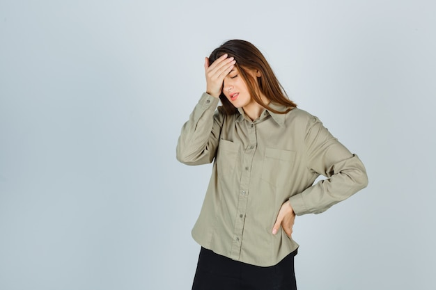 Cute young female in shirt, skirt suffering from migraine and looking annoyed , front view.