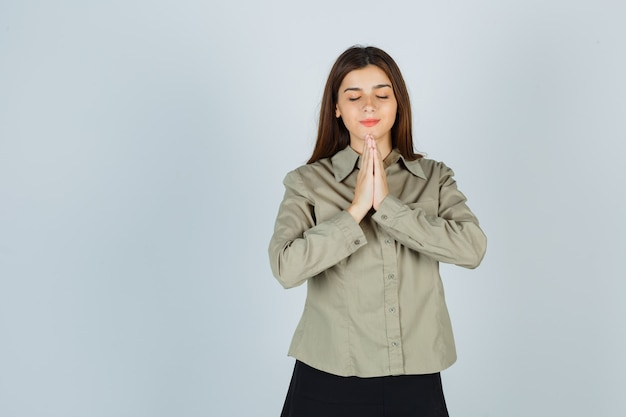 Cute young female showing namaste gesture in shirt, skirt and looking hopeful , front view.