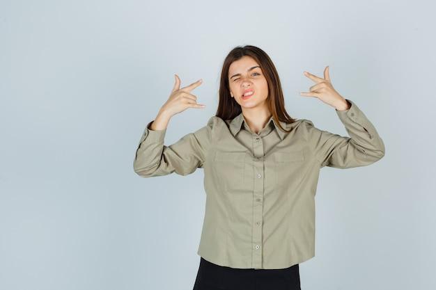 셔츠, 치마를 입고 생각에 잠긴 표정을 짓고 있는 동안 바위 제스처를 보여주는 귀여운 젊은 여성. 전면보기.