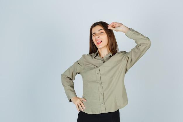 Симпатичная молодая женщина показывает жест салюта, подмигивая в рубашке и выглядит уверенно. передний план.
