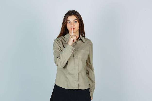 Carino giovane donna che mostra gesto di silenzio in camicia, gonna e guardando attenta, vista frontale.