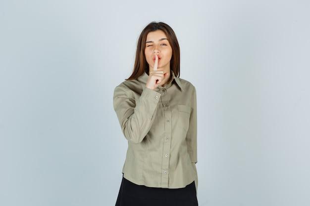 귀여운 젊은 여성이 셔츠, 치마를 입고 현명하게 보이는 동안 침묵 제스처를 보여줍니다. 전면보기.