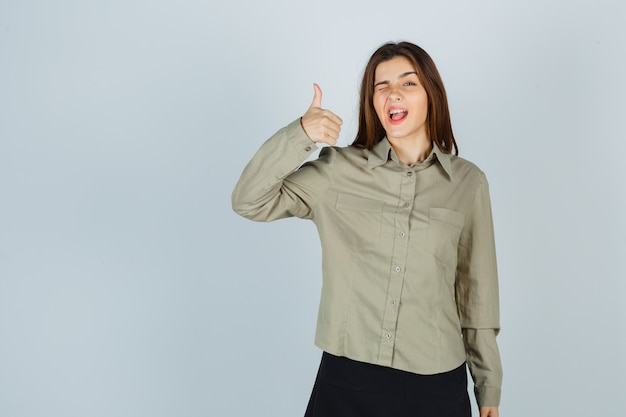 Симпатичная молодая женщина показывает палец вверх, мигая в рубашке, юбке и гордо глядя, вид спереди.