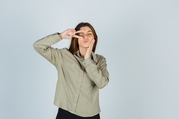まばたき、唇をふくれっ面、シャツの頬に手を握り、自信を持って見ながら目の近くにvサインを示すかわいい若い女性。正面図。